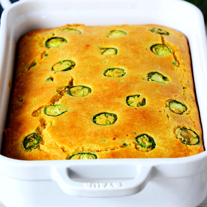 Jalapeno Cheddar Cornbread in a white casserole dish with jalapenos on top.