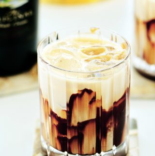 Mudslide cocktail with a chocolate garnish in a rocks glass with a bottle of Baileys and an ice bucket in the background.