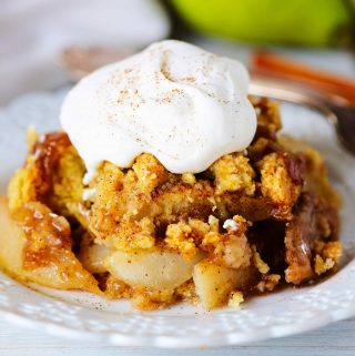 Pear cobbler topped with whipped cream and cinnamon on a white plate with a fork and pears behind it.