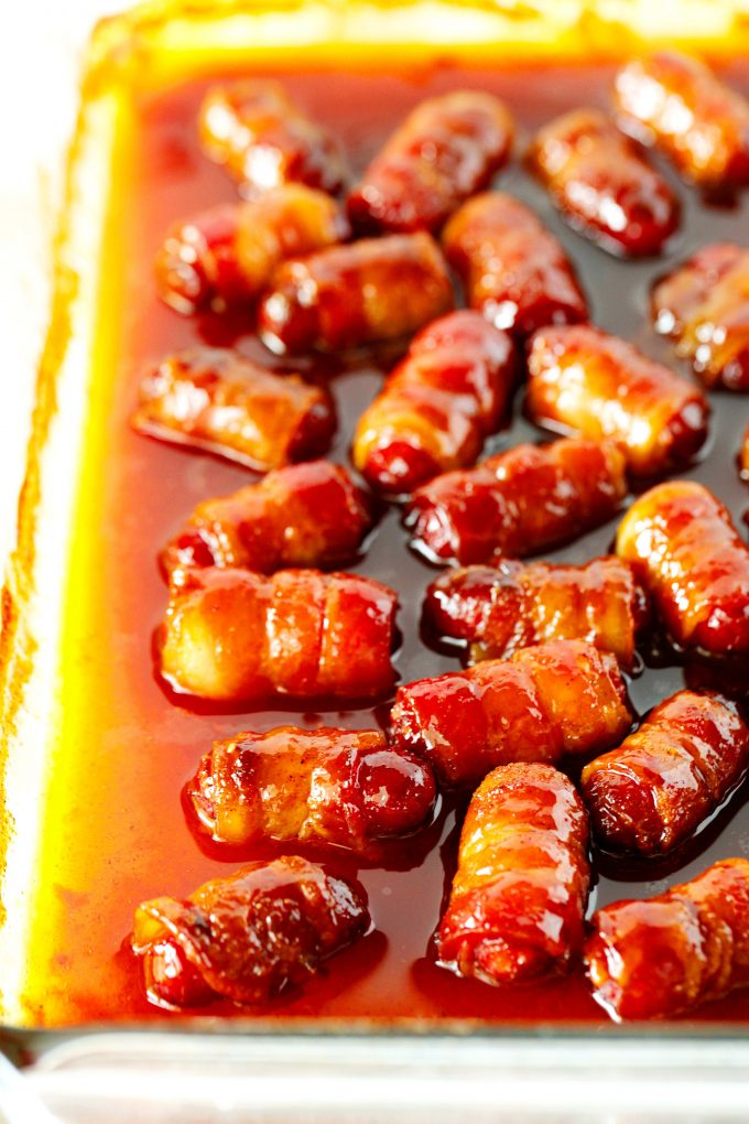 Bacon wrapped smokies with a brown sugar glaze in a casserole dish.