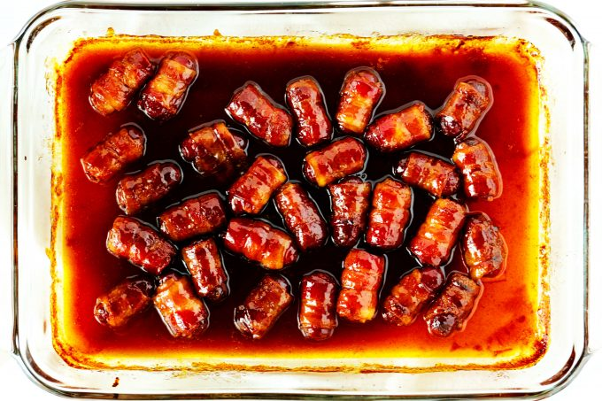 An overhead shot of bacon wrapped smokies with a brown sugar glaze in a casserole dish.
