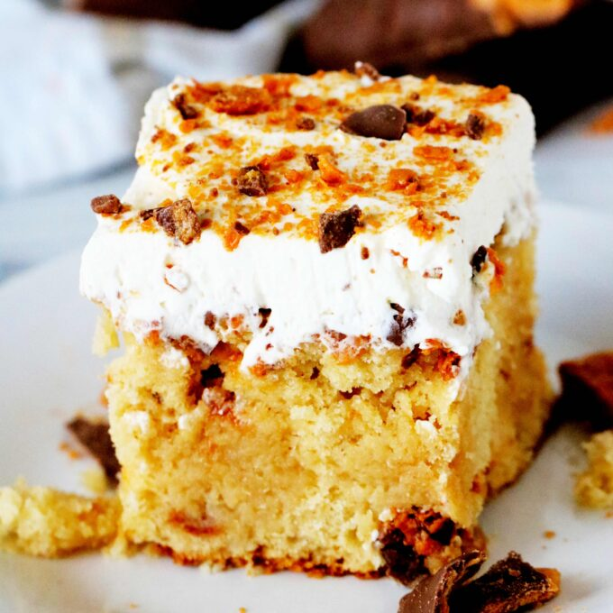 A slice of Butterfinger Cake on a white plate.