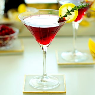 A pomegranate martini with a lemon wheel wedge and rosemary garnish.