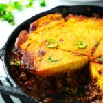 Tamale Pie in a skillet with a slice cut out of it.