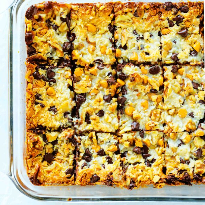 An overhead close up shot of 7 Layer Magic Bar Cookies cut into bars in a casserole dish.