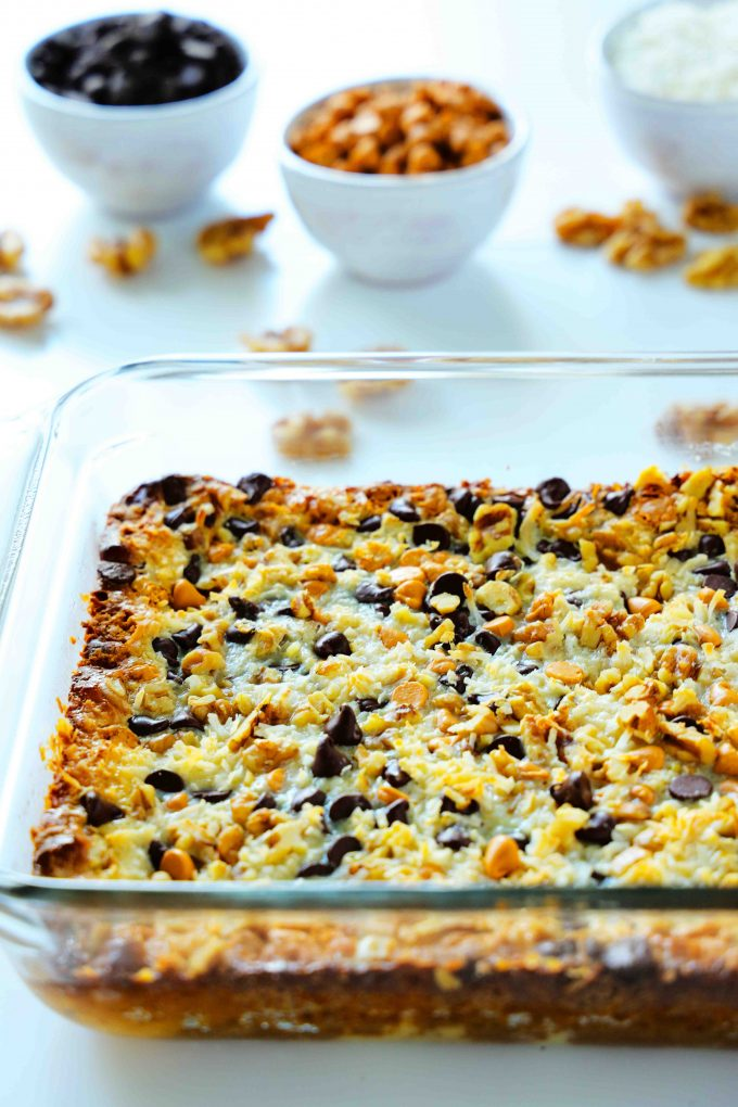 """7 Layer Bars in a 9x13"""" casserole dish with bowls of baking chips behind it."""