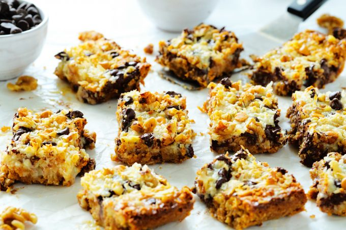 Cut up 7 Layer Bars on a sheet of parchment paper.
