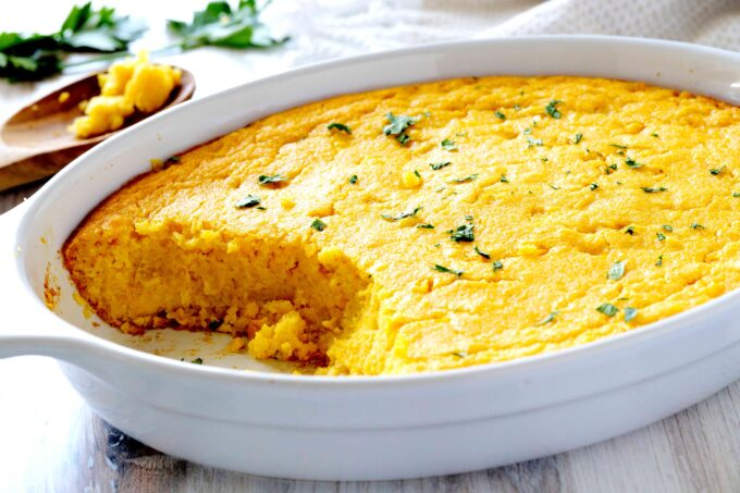 Cornbread Pudding in a white dish with a spoon off to the side.