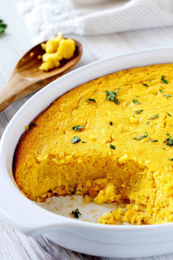 Corn pudding in a white dish with a spoon holding corn pudding and a napkin off to the side.