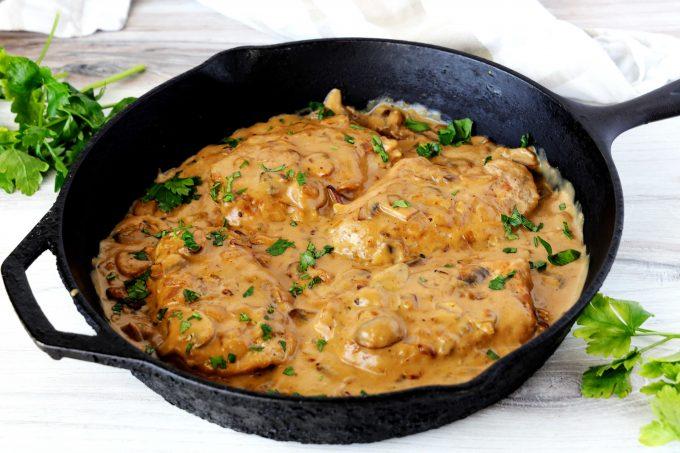 Pork chops with mushroom gravy in cast iron pan.