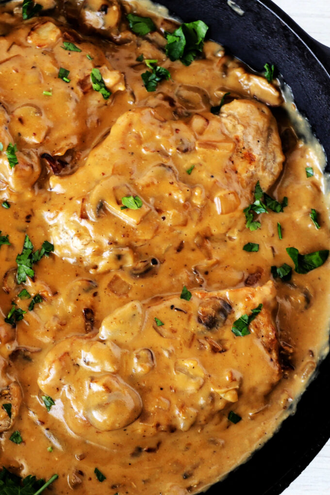A close up, overhead shot of pork chops with mushroom gravy in cast iron pan.