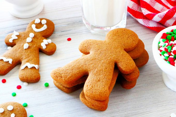 A stack of undecorated gingerbread cookies on a white background with milk and sprinkles and decorated cookies surrounding them.