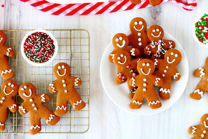 An overhead shot of gingerbread men on a cooling rack and a plate of gingerbread men off to the side.
