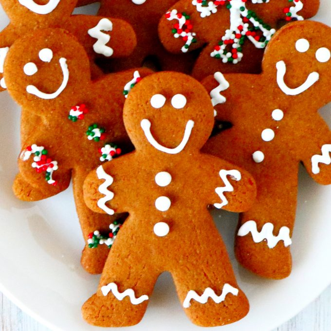 A close up, overhead shot of decorated gingerbread cookies on a white plate.
