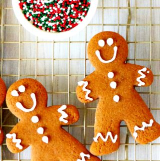 Two gingerbread cookies on a cooling rack with a bowl of sprinkles off to the side.