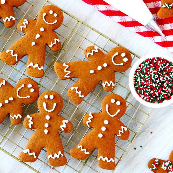 An overhead shot of gingerbread cookies on a cooling rack with a piping bag of icing and sprinkles off to the side.