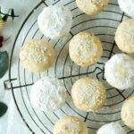 An overhead shot of Italian Wedding Cookies, some with icing and other rolled in powdered sugar, on a rack.