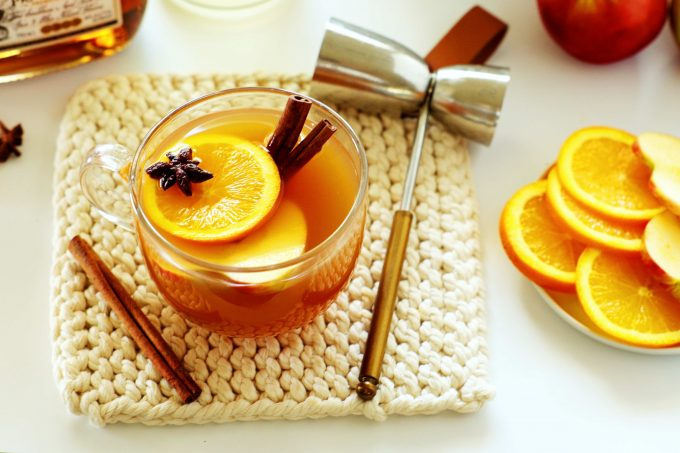 A mug of spiked apple cider with a bar tool off to the side and a plate of orange wheels and scattered cinnamon sticks.