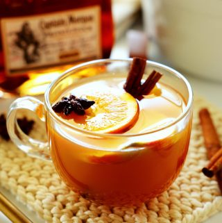 A mug of spiked apple cider with star anise, cinnamon sticks, and orange sliced