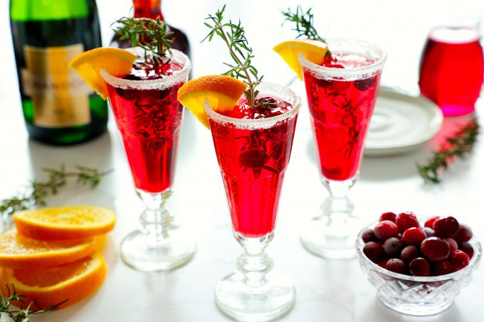 Three cranberry mimosas with a sugar rim and an orange, rosemary, and cranberry garnish with a plate of sugar and a bowl of cranberries in the background. There are also some orange wedges and a bottle of champagne off to the side.