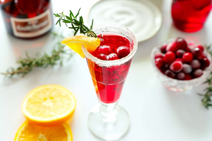 A cranberry mimosa with a sugar rim and an orange, rosemary, and cranberry garnish with a plate of sugar and a bowl of cranberries in the background. There are also some orange wedges and a bottle of Grand Marnier off to the side .
