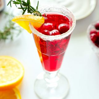 A cranberry mimosa with a sugar rim and an orange, rosemary, and cranberry garnish with a plate of sugar and a bowl of cranberries in the background. There are also some orange wedges off to the side.