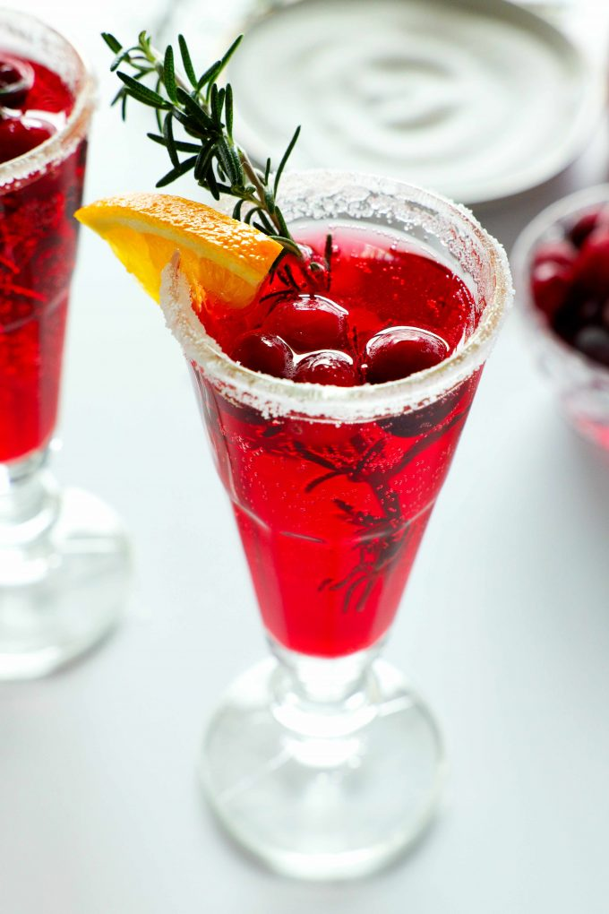 A cranberry mimosa with a sugar rim and an orange, rosemary, and cranberry garnish with a plate of sugar and a bowl of cranberries in the background.