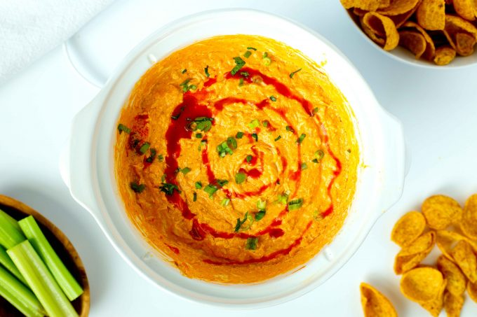 An overhead shot of crockpot buffalo chicken dip with a bowl of fritos and celery sticks beside it.