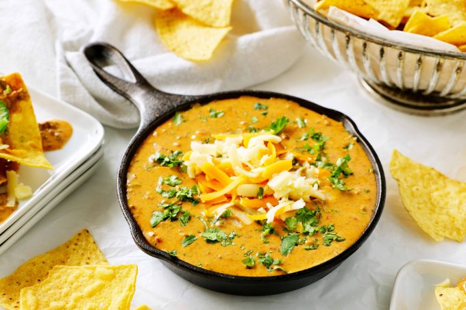 Chili cheese dip in a skillet topped with shredded cheese and chopped cilantro with chips and plates off to the side.