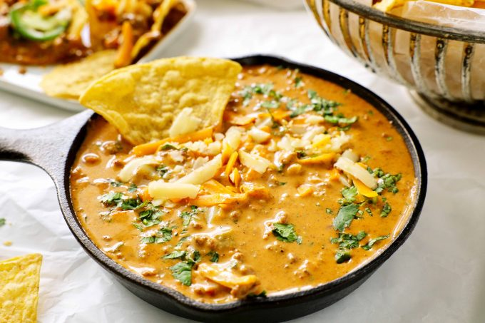 A skillet of chili cheese dip with a chip sticking out of it.