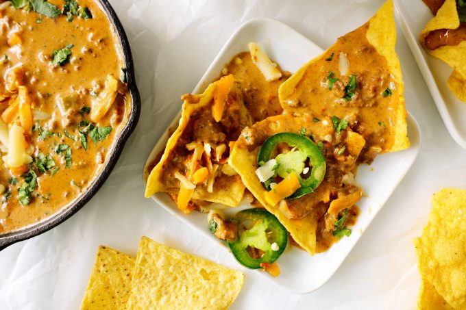 An overhead shot of chips topped off with chili cheese dip and sliced jalapenos with a skillet of cheese dip off to the side.