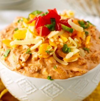 A close up shot of cream cheese dip with salsa mixed in and taco toppings on top.