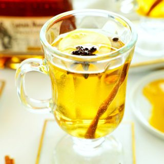 Hot toddy with rum with a lemon wheel, star anise, and whole allspice in it in a mug, sitting on a coaster. There is a bottle of rum in the backgroudn and star anise beside it. There is also a plate of honey off to the side.