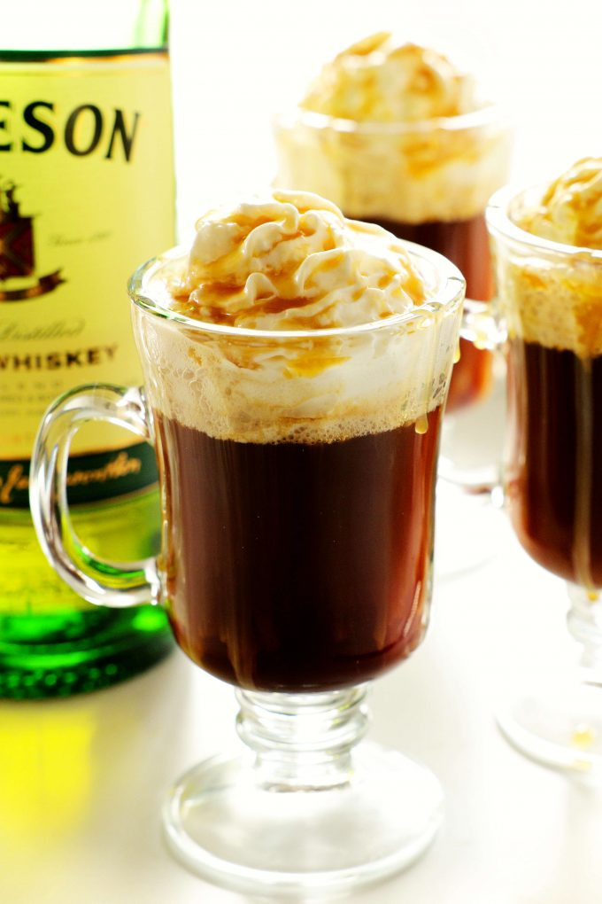 Three irish coffees topped with whipped cream and caramel with a bottle of whiskey off to the side.