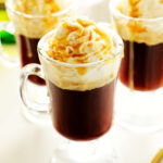 Three irish coffees topped with whipped cream and caramel.