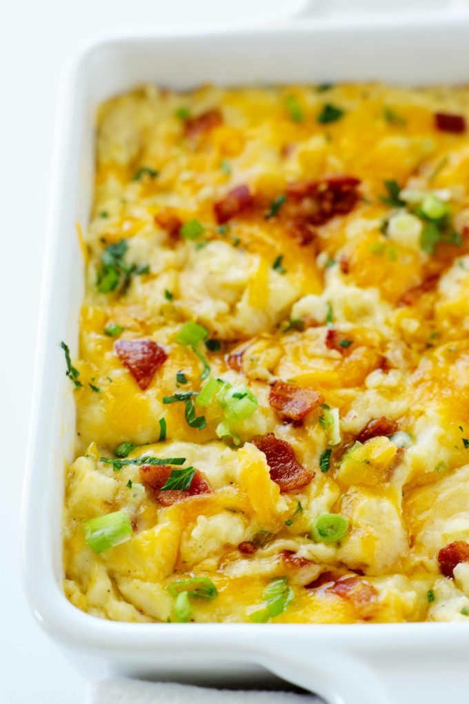 A close up shot of Twice Baked Mashed Potatoes topped with cheese, bacon, parsley, and chives in a casserole dish.
