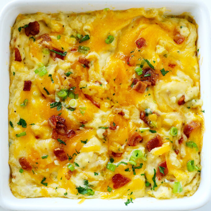 An overhead shot of Twice Baked Mashed Potatoes in a white casserole dish.