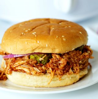 A BBQ Pulled Chicken Sandwich on a white plate with onions in the background.