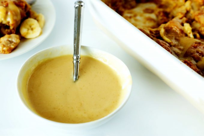 Vanilla sauce in a white bowl with a spoon inside of it.