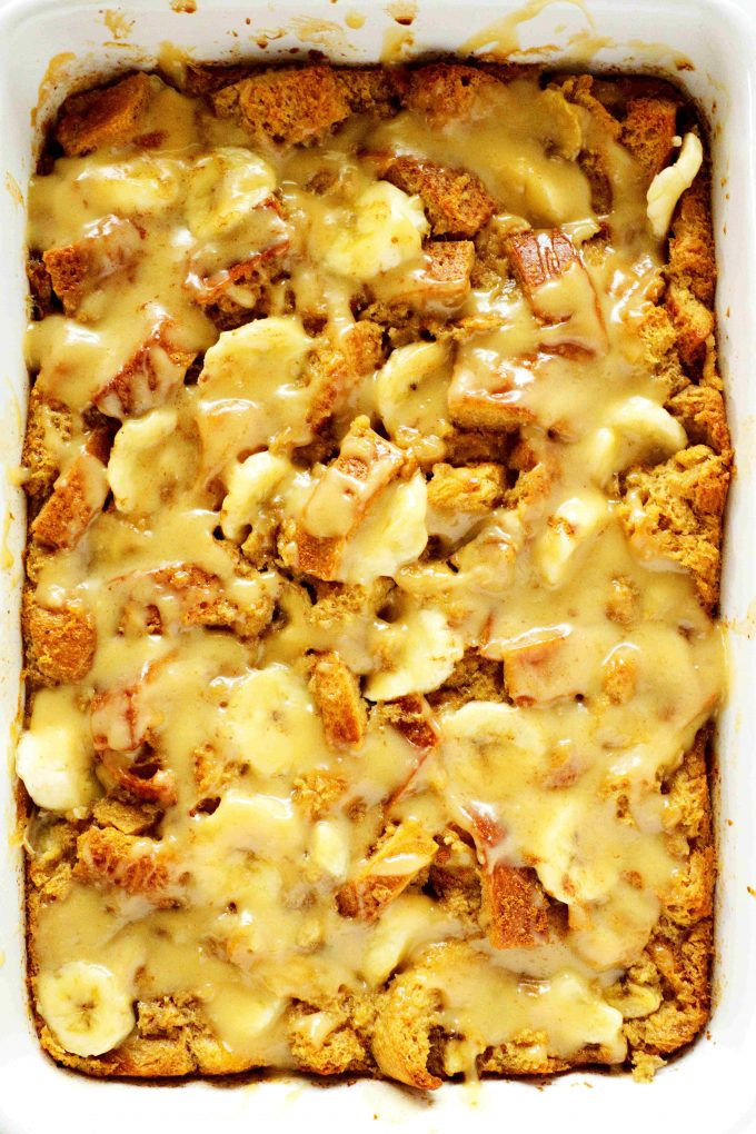 An overhead shot of a casserole dish full of banana bread pudding with vanilla sauce on top.