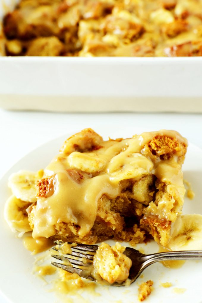 A slice of banana bread pudding on a white plate with vanilla sauce on top and a casserole dish behind it.