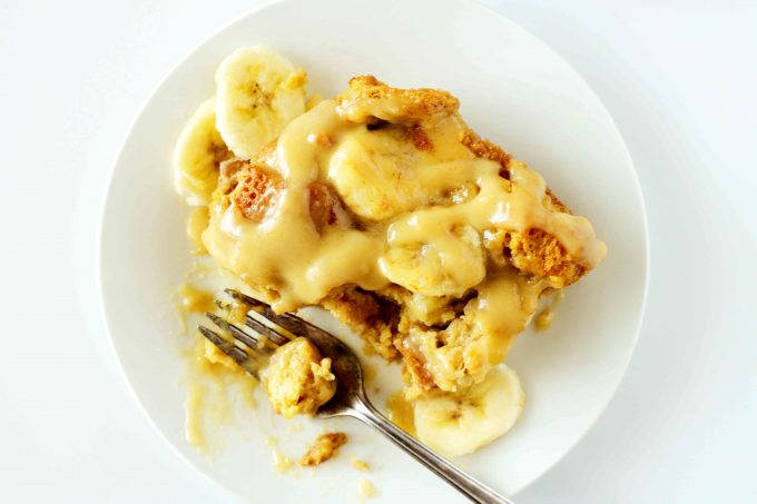 An overhead shot of a slice of banana bread pudding on a white plate with vanilla sauce on top. A fork is off to the side with a bite taken out of it.
