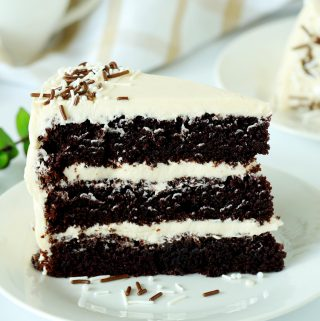 A slice of chocolate coffee cake with buttercream frosting on a white plate.