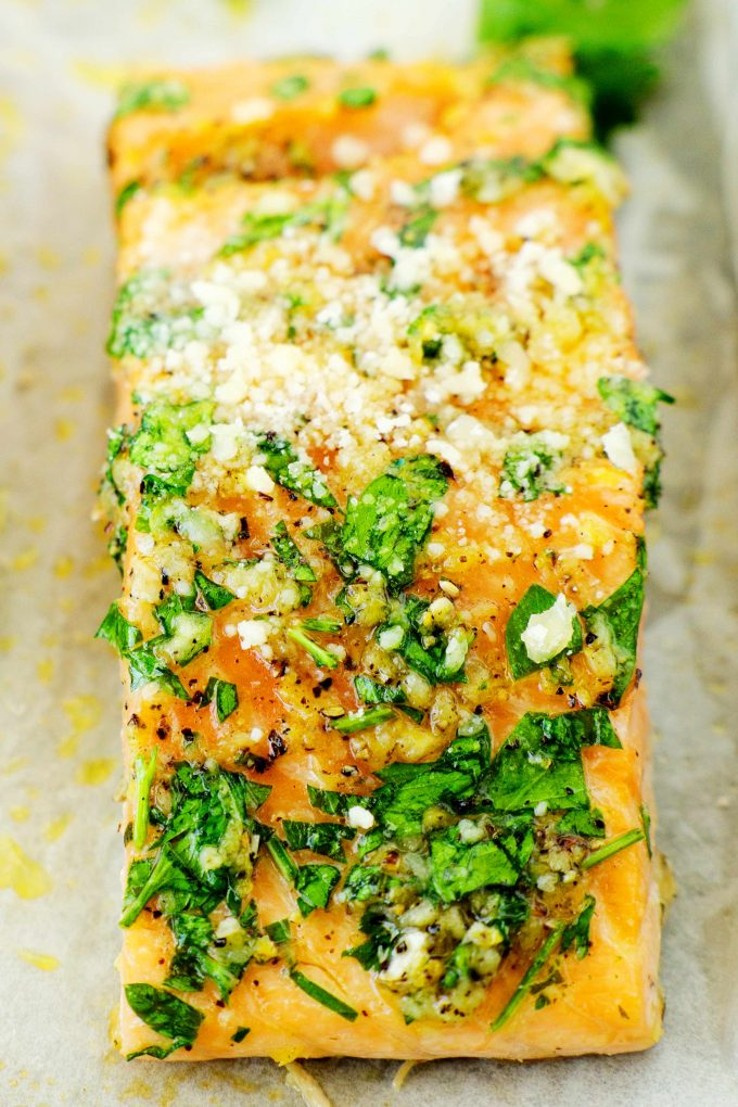A close up shot of Lemon Garlic Salmon topped with parsley on a sheet of white parchment paper.