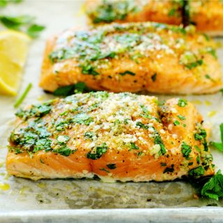 Individual fillets of Lemon Garlic Salmon laid out on a baking sheet with a lemon wedge off to the side.