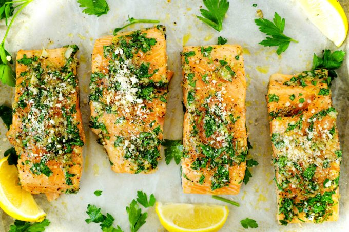 Lemon Garlic Salmon topped with parsley on a sheet of white parchment paper with lemons and parsley sprigs around it.