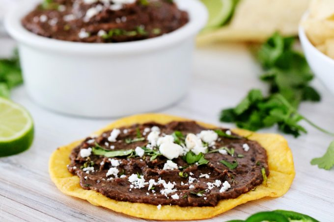 Refried black beans smeared on a tostada shell and topped with cheese and cilantro.
