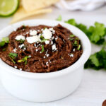 Refried Black Beans in a white bowl topped with cilantro and crumbled cheese. There are sprigs of cilantro, limes, and tortilla chips in the background.