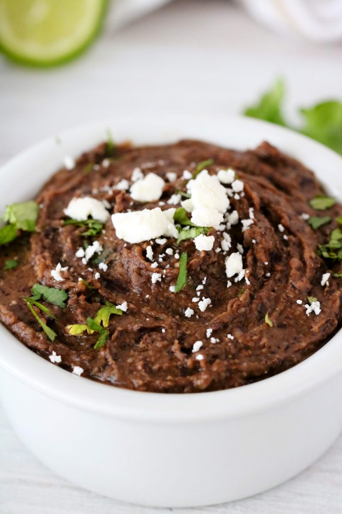 A close up of refried black beans with cilantro and crumbled cheese on top.