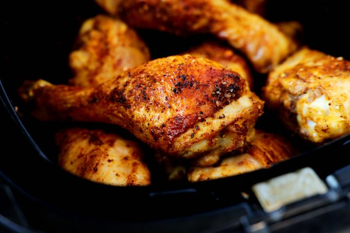 Cooked chicken legs stacked in the basket of an air fryer.